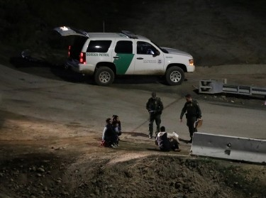 U.S. Customs and Border Protection officials detain migrants from Central America after they crossed from Mexico, at the International Friendship Park in San Diego county, CA, January 16, 2019, photo by Mohammed Salem/Reuters