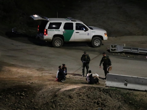 U.S. Customs and Border Protection officials detain migrants from Central America after they crossed from Mexico, in San Diego County, CA, January 16, 2019