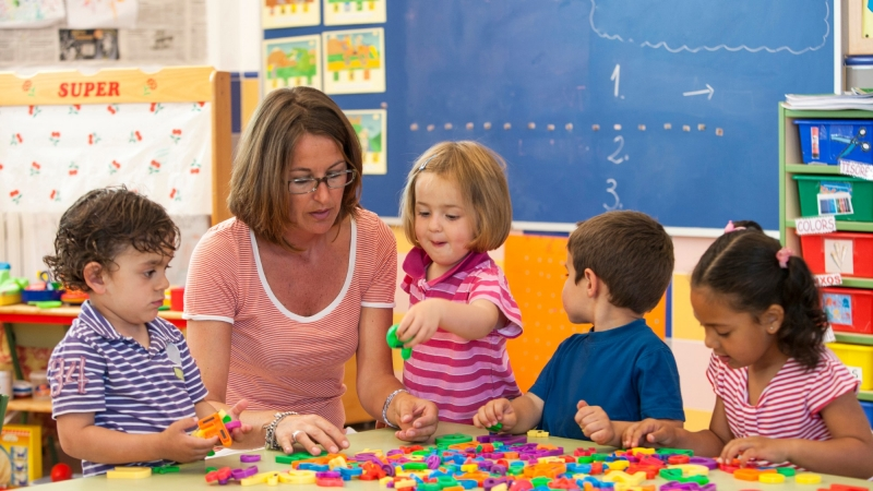 Female teacher with preschool boys and girls learning alphabet in classroom
