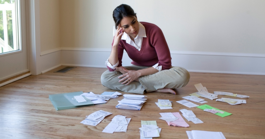 Woman seated on the floor, surrounded by bills and receipts, photo by David Sacks/Getty Images