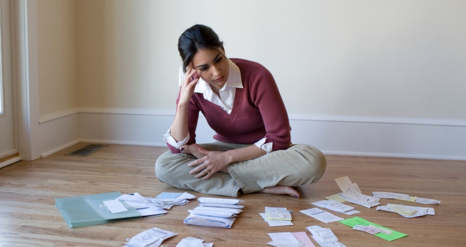 Woman sitting on the floor surrounded by bills and receipts
