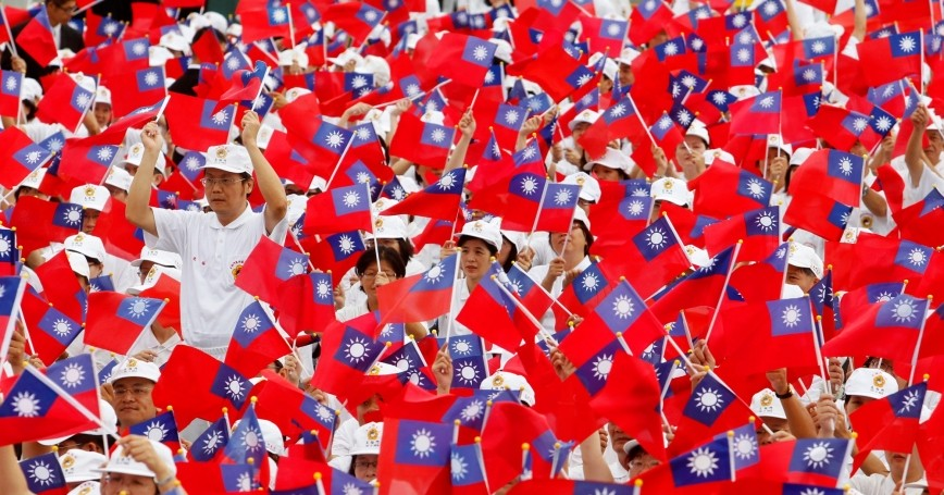 Participants wave flags during Taiwan's National Day celebrations outside the Presidential Office in Taipei, Taiwan, October 10, 2010, photo by Nicky Loh/Reuters