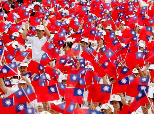 Participants wave flags during Taiwan's National Day celebrations outside the Presidential Office in Taipei, Taiwan, October 10, 2010