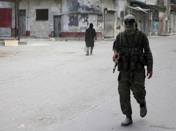 Members of al Qaeda's Nusra Front walk along a street in the northwestern city of Ariha, after a coalition of insurgent groups seized the area in Idlib province, May 29, 2015, photo by Abed Kontar/Reuters