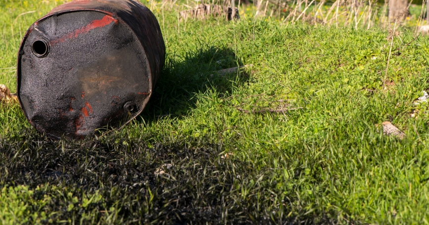 Oil barrel leaking oil grass, photo by RuslanDashinsky/Getty Images