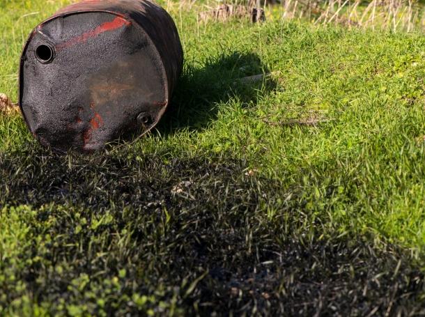 Oil barrel leaking oil grass, photo by RuslanDashinsky/Getty Images