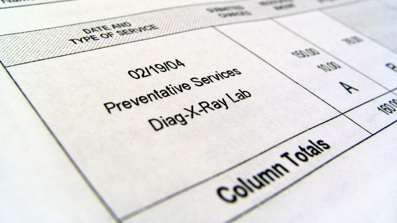 Medical bill showing charges for preventative services and x-rays, photo by lbodvar/Getty Images