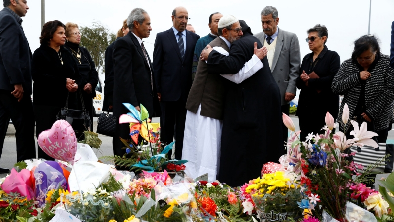 Imam Ibrahim Abdul Halim of the Linwood Mosque is embraced by Father Felimoun El-Baramoussy from the Coptic Church, in Christchurch, New Zealand March 18, 2019, photo by Edgar Su/Reuters