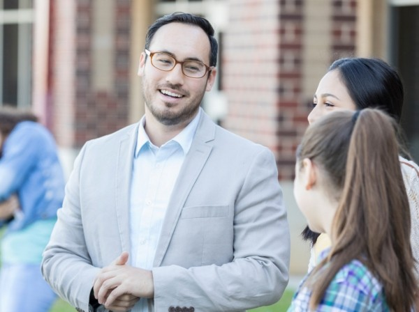 High school principal talks with students outside at school, photo by asiseeit/Getty Images