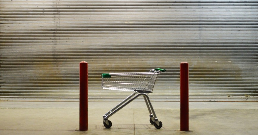 A grocery cart in front of a closed supermarket, photo by galbiati/Getty Images