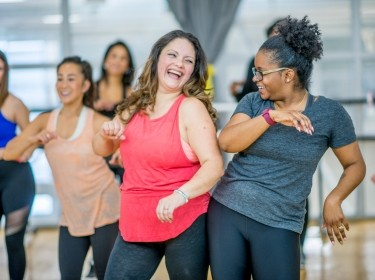 Women dancing in a gym, photo by FatCamera/Getty Images