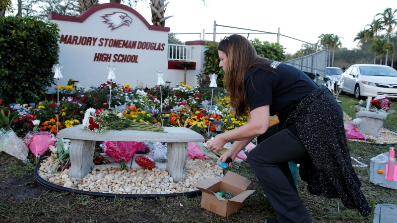 Suzanne Devine Clark places items on a memorial on the one year anniversary of the shooting which claimed 17 lives at Marjory Stoneman Douglas High School in Parkland, Florida, U.S., February 14, 2019, photo by Joe Skipper/Reuters