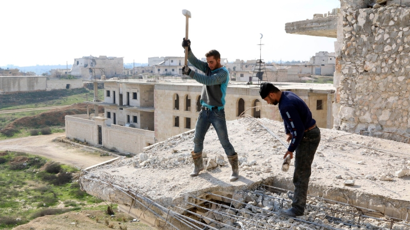 Men work on a damaged building in the northwestern province of Idlib, Syria, December 27, 2014, photo by Mahmoud Hebbo/Reuters