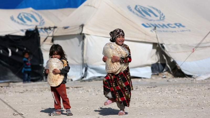 Children walk as they hold stacks of bread at al-Hol displacement camp in Hasaka governorate, Syria, April 2, 2019, photo by Ali Hashisho/Reuters