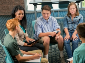 Students and a counselor sit in a circle, photo by Steve Debenport/Getty Images