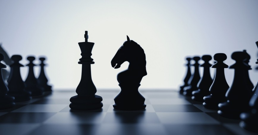 Chess pieces on a board, photo by phaisarn2517/Getty Images