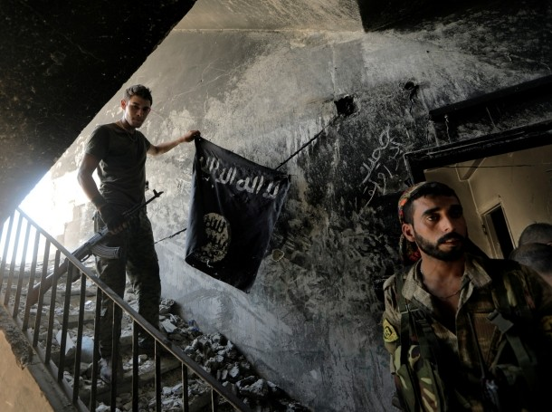 Members of the Syrian Democratic Forces with a captured ISIS flag in Raqqa, Syria, August 14, 2017, photo by Zohra Bensemra/Reuters