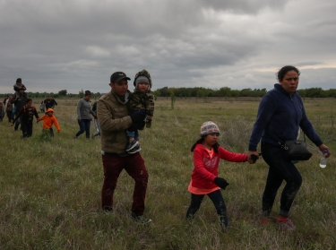 Asylum seeking migrant families from Central America in a field after crossing the Rio Grande river into the U.S. from Mexico in Penitas, Texas, March 31, 2019, photo by Adrees Latif/Reuters