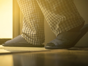 A person in pajamas and slippers walking to the bathroom at the night, photo by Sergey Dogadin/Getty Images
