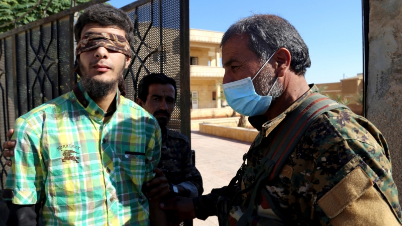 A member of the Syrian Democratic Forces escorts a blindfolded civilian detainee suspected to be a member of Islamic State militants in Raqqa, October 12, 2017, photo by Issam Abdallah/Reuters