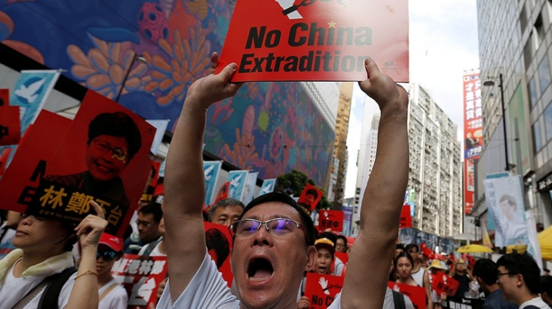 A demonstrator holds up a sign during a protest to demand authorities scrap a proposed extradition bill with China, in Hong Kong, China June 9, 2019, photo by Thomas Peter/Reuters