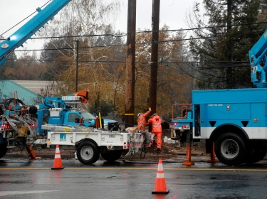 PG&E works on power lines to repair damage caused by the Camp Fire in Paradise, California, November 21, 2018, photo by Elijah Nouvelage/Reuters