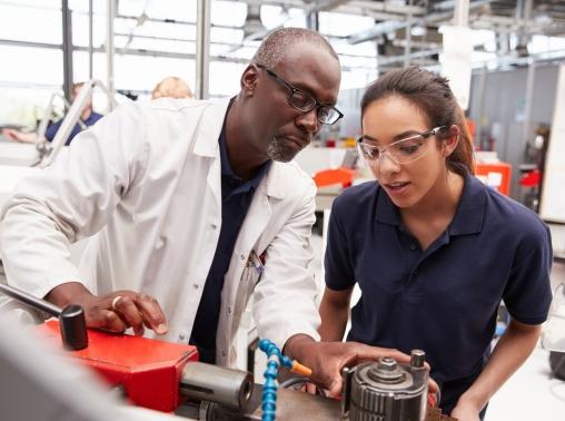 An engineer teaching an apprentice