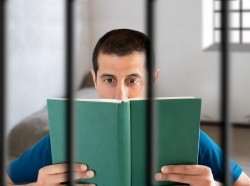 Man reading in prison cell, photo by Manuel-F-O/Getty Images
