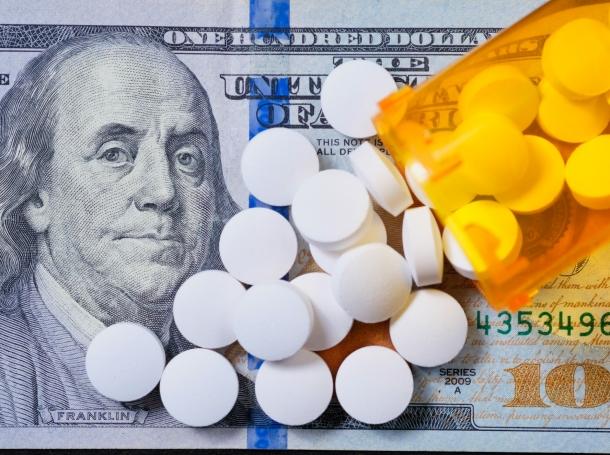 White prescription pills on a U.S. $100 bill, photo by Stuart Ritchie/Getty Images
