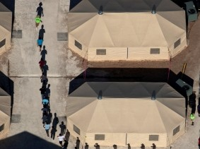 Immigrant children are led by staff in single file between tents at a detention facility near the Mexican border, Tornillo, Texas, June 18, 2018, photo by Mike Blake/Reuters