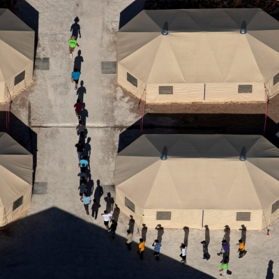 Immigrants are escorted to a tent that serves a dining hall for the U.S. government's newest holding center for migrant children in Carrizo Springs, Texas, July 9, 2019, photo by Eric Gay/Reuters