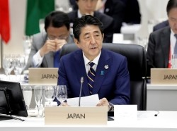 Japan's Prime Minister Shinzo Abe speaks during a working lunch at the Group of 20 (G-20) summit in Osaka, Japan, on Friday, June 28, 2019, photo by Kiyoshi Ota/Reuters