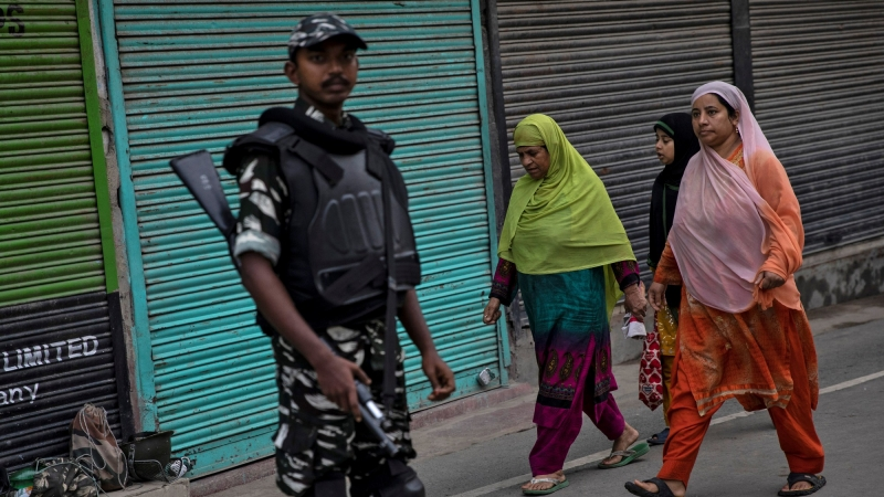 Kashmiri women walk past an Indian security personnel during restrictions after the scrapping of the special constitutional status for Kashmir by the government, in Srinagar, August 11, 2019, photo by Danish Siddiqui/Reuters
