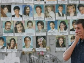 A relative grieves at Beslan school No.1 at a wall with portraits of victims of school siege that took the lives of 331 people, in Beslan, Russia, September 1, 2005, photo by Sergei Karpukhin/Reuters
