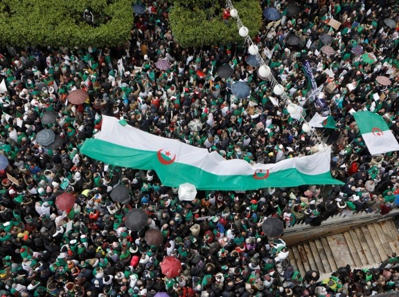 People carry banners and Algerian national flags during a protest calling on President Abdelaziz Bouteflika to quit, in Algiers, Algeria, March 22, 2019, photo by Zohra Bensemra/Reuters