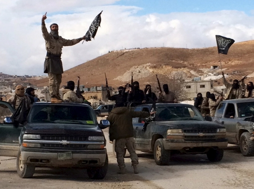 Al Qaeda-linked Nusra Front fighters carry weapons on the back of pick-up trucks in Arsal, eastern Bekaa Valley, Lebanon, December 1, 2015