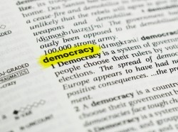 "Detail of the english word ""democracy"" highlighted and its definition from the dictionary, photo by Lobro78/Getty Images"