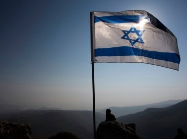 An Israeli soldier stands guard under an Israeli national flag in the Jordan Valley near the Jewish settlement of Maale Efrayim, January 2, 2014, photo by Ronen Zvulun/Reuters