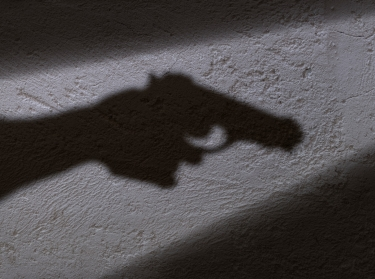 A shadow of a hand holding a gun, photo by ugurhan/Getty Images