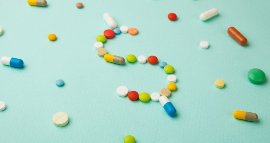 A variety of prescription pills and capsules formed into a dollar sign