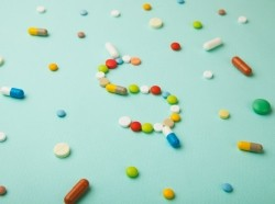 A variety of prescription pills and capsules formed into a dollar sign, photo by ADragan/Getty Images