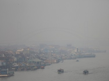 Boats on the Musi River which was shrouded in smoke following an increase in fires in the region in Palembang, South Sumatra, Indonesia, September 16, 2018, photo by Antara Foto/Nova Wahyudi/Reuters