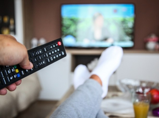 Hand holding remote pointing at a TV, photo by Milan Markovic/Getty Images