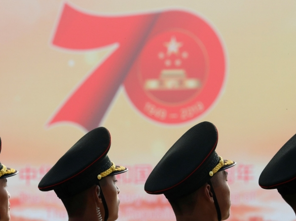 People's Liberation Army soldiers are seen in front of a sign marking China's 70th anniversary before a military parade in Beijing, October 1, 2019, photo by Thomas Peter/Reuters