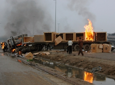 Iraqis watch as a truck burns on a roadside after an attack by suspected insurgents on a highway west of Baghdad February 15, 2006, photo by Stringer/Reuters
