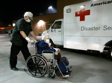 An elderly couple leaves an evacuation center as a wildfire forces the center itself to be evacuated, Poway, California, October 21, 2007, photo by Mike Blake/Reuters