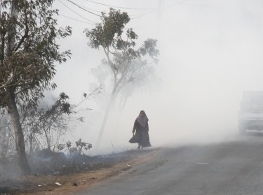 A woman walks along a road covered in smog due to a forest fire in Banjarbaru, South Kalimantan province, Indonesia, September 6, 2019, photo by Antara Foto Agency/Reuters