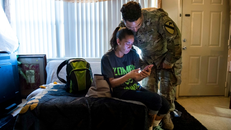 An Army couple reacts to local residents' posts regarding housing issues on a community Facebook group at their army base home in Fort Hood, Texas, May 16, 2019, photo by Amanda Voisard/Reuters