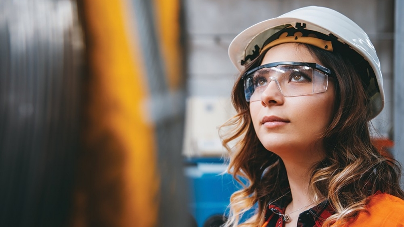 Woman wearing safety glasses and a hardhat looks at a machine