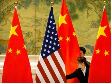 Chinese staffers adjust U.S. and Chinese flags before the opening session of trade negotiations between U.S. and Chinese trade representatives in Beijing, February 14, 2019, photo by Mark Schiefelbein/Reuters